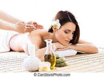 Young woman on a massage procedure - Beautiful woman laying...