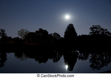 Moonrise over lake - Rising full moon and trees are...