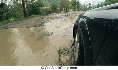 Driving damaged road with puddles after rain - Driving...
