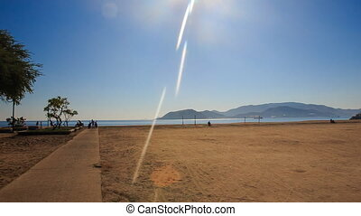 camera moves along path across wide sand beach to azure sea...
