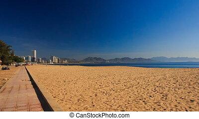 camera moves past beach with sunshade parasols at dawn -...
