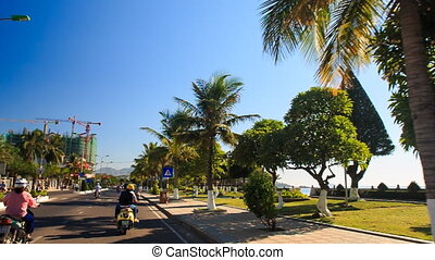 camera moves among traffic past palms embankment