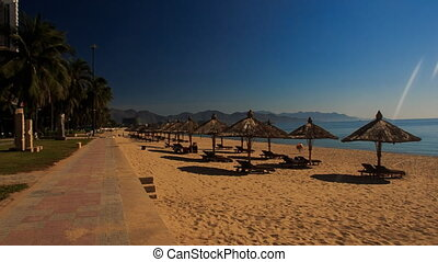 camera moves past wide beach with sunshade parasols in...