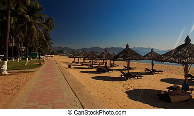 camera moves past beach with sunshade parasols at sunrise -...