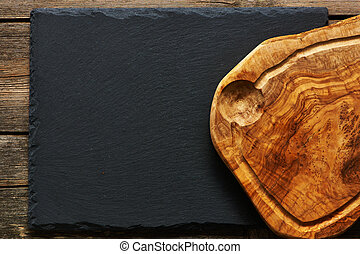 Olive wood cutting board over slate