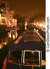Docked boat at night - Canal with tour boat at night in...