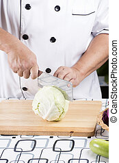 Chef cutting cabbage on the wooden broad