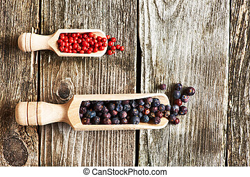 Juniper berries and rose pepper - Wooden scoops with dried...
