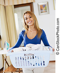 woman doing laundry - woman holding basket of laundry and...