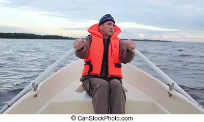 Man in a life jacket at the oars