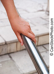 Woman hand on handrail - Woman hand using a handrail. Urban...