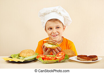 Little funny chef appetizing licked near cooked hamburger -...