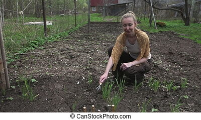 Young pretty woman looks after behind plants in garden -...