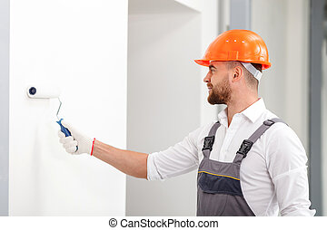 Cheerful male builder is making house beautiful