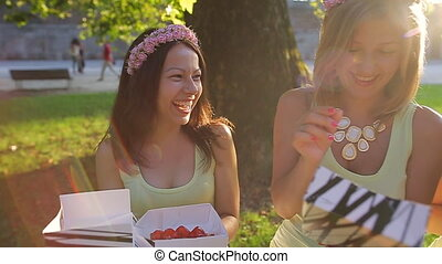 beautiful girl eats sweets in the park