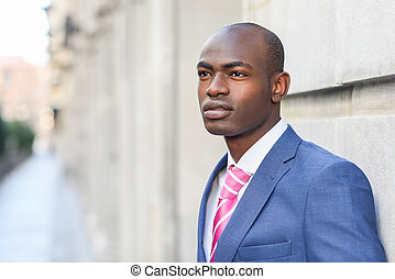 Handsome black man wearing suit in urban background -...