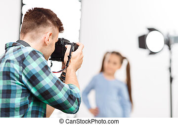 Young photographer is busy during photoshoot - Photographer...
