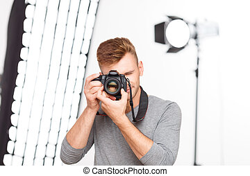 Handsome male professional upholds his camera - Photographer...