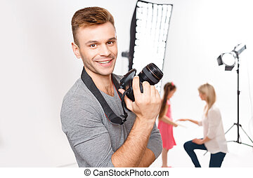Handsome male photographer smiles while upholding his camera...