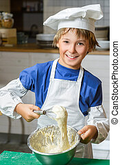 Funny happy chef boy cooking at restaurant kitchen and knead...