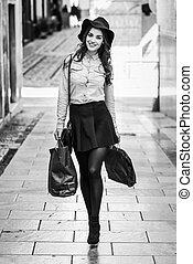 Woman walking on the street with shopping bags - Beautiful...