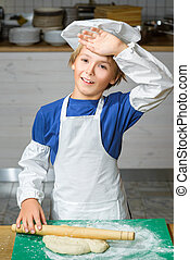 Funny happy chef boy cooking at restaurant kitchen and rolls...
