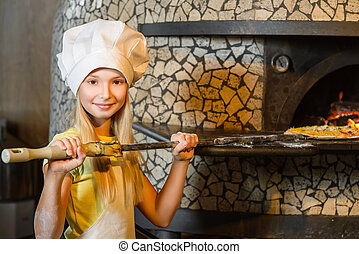 Funny happy chef girl cooking at restaurant kitchen and puts...