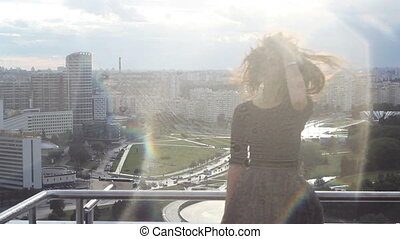 Beautiful woman enjoying the sunset from the roof - Young...