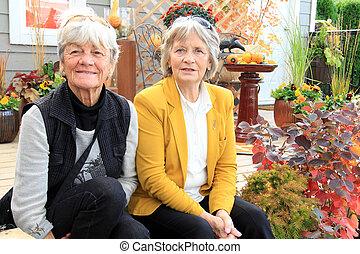 Two senior ladies seated on a patio - Two senior ladies, age...