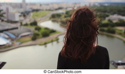 Beautiful woman enjoying the sunset from the roof