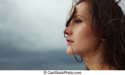 Wind blowing hair of beautiful young woman