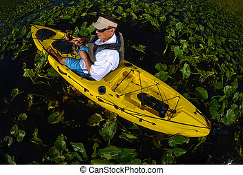 man kayak fishing in lily pads in yellow kayak