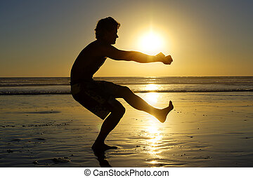 Beach air squats - Silhouette of fit shirtless man doing one...