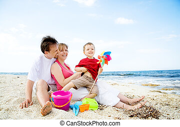 Happy family having fun on the beach. Plenty of copy space.