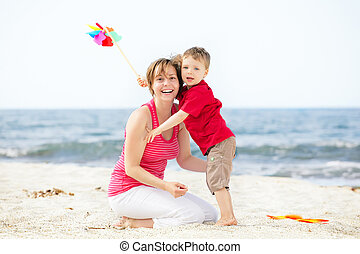 Mother and son having fun on the beach. Plenty of copy...
