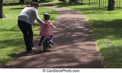 Teaching child to ride bicycle - Parent (Young mother age...