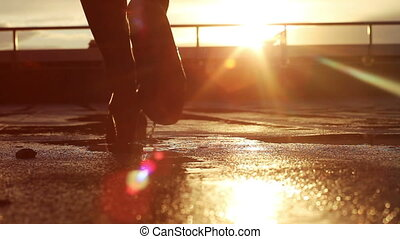 Legs of woman on the road after rain in the sunset - Legs of...