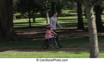 Drive-iTeaching child to ride bicyc - Parent Young mother...