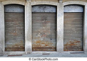 lowered rolling shutters of a disused shop, rusty, dirty and...