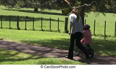 Teaching child to ride bicycle - Parent Young mother age 30...