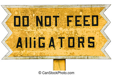 Yellow wooden warning sign with black text. Do not feed Alligators.