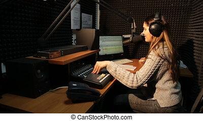 Beautiful Radio DJ in studio talking with audience