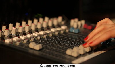 Hand DJ on a mixer, operating the leader