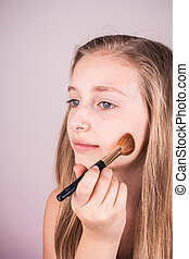 Portrait of beautiful blond girl, makeup brush trying to...