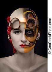 Bald girl with a art make up and steampunk glasses, on the...