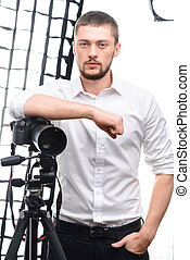 Young attractive photographer leaning on tripod camera -...
