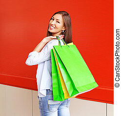 Beautiful smiling woman with shopping bags in city over colorful red background