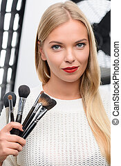 Makeup artist showing professional brushes.