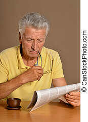 Man reading newspaper - Senior man reading newspaper at a...