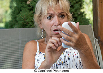 Blond senior woman is surprised to horrified from what she...